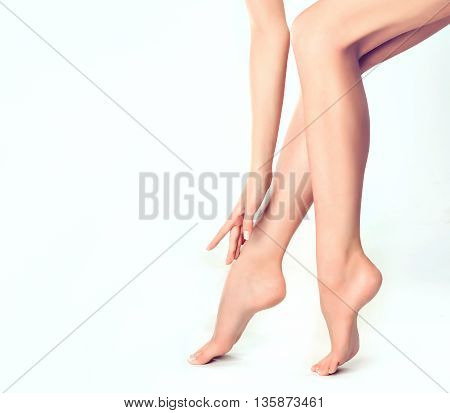 Beautiful well-groomed female legs . Foot care . Epilation and depilation of hair on the feet . Smooth long slender bare feet
