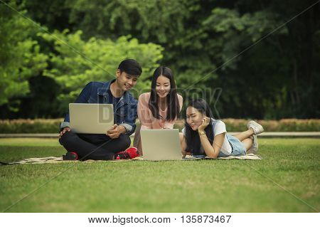 Friends teens are using a laptop computer in the outdoors.