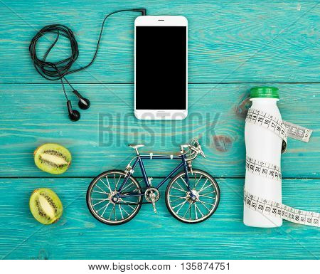 Bicycle Model, Headphones, Smartphone, Kiwi, Bottle Of Water And Centimeter Tape On Blue Wooden Desk