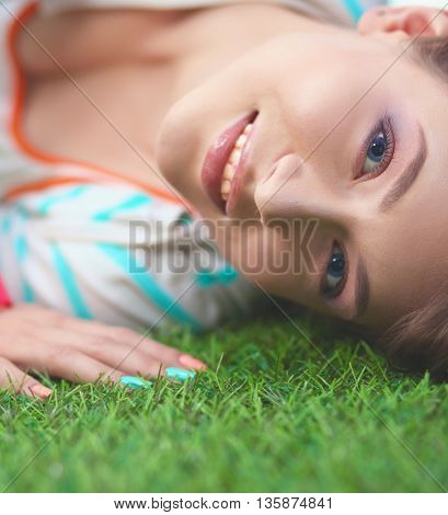 Beautiful young woman lying on the green grass