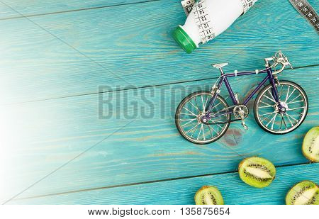 Sport Concept -  Bicycle Model, Bottle Of Water, Kiwi And Centimeter Tape