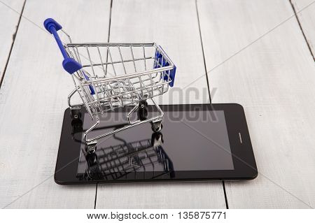 Shopping Cart On Tablet Pc On White Wooden Background