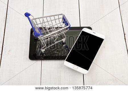 Shopping Cart On The Tablet Pc Near To Smartphone On A White Wooden Desk