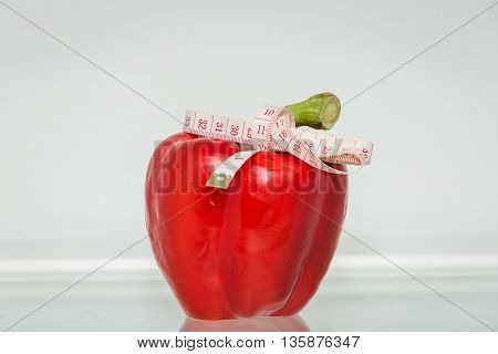 Red sweet pepper with measuring tape. Healthy eating. Healthy lifestyle. Diet. Source of vitamins. Vegetarian. Weight loss