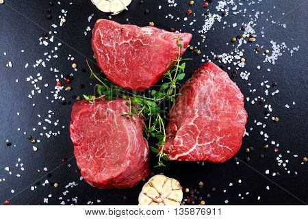 Fresh Raw Beef steak Mignon, with salt, peppercorns, thyme, garlic Ready to cook