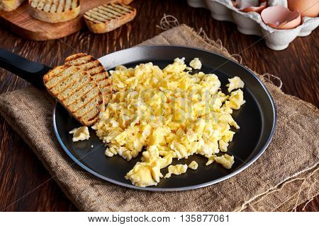 Homemade rustic breakfast Scrambled eggs on Pan with grilled toast