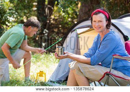 Senior couple relaxing beside their tent in the forest