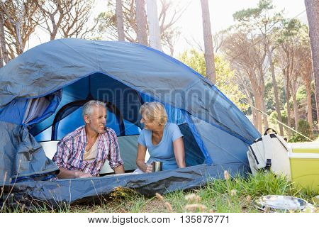 Mature couple sitting and looking each other on camp site