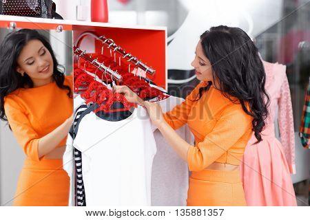 Young woman buys a white T-shirt. Woman shopping for dress in clothing retail store. Caucasian shopper girl in shop during sale. Woman shopping for dress. Fashion shopping