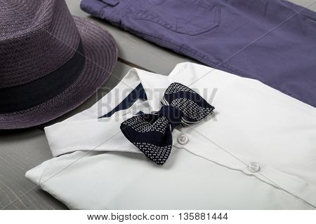 Men's outfit on wooden background. Kids fashion clothes. Grey fedora navy pant white shirt balck bow tie for boy. Close up.