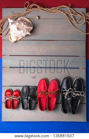 Family boat shoes on wooden background. Four pair of red and black boat shoes on grey desk with rope and shell. Top view copy space. family concept
