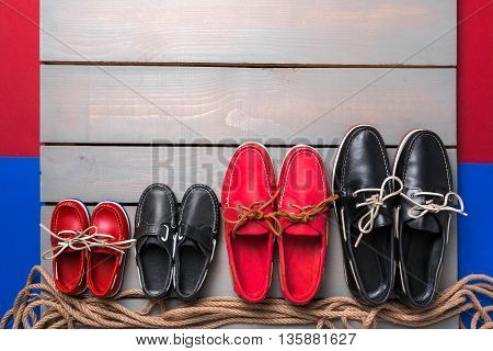 Family boat shoes on wooden background. Four pair of red and black boat shoes on grey desk with rope. Top view copy space. family concept