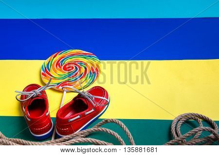 Small red boat shoes near big multi-colored lollipop and rope on colored background. Back view. Copy space frame