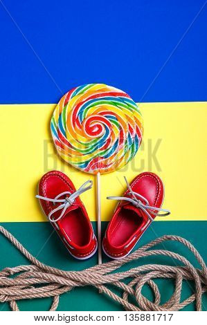Small red boat shoes near big multi-colored lollipop and rope on colored background. Top view. Close up.