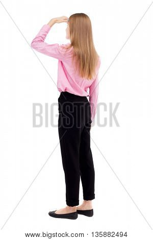 back view standing young beautiful  woman. Rear view people collection. backside view person. girl office worker in black trousers stands sideways and looks thoughtfully left put her hand to her eyes.