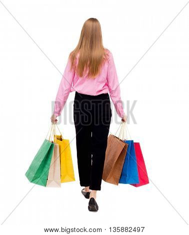 back view going  woman  with shopping bags. beautiful girl in motion. backside view of person. Rear view people collection. Isolated over white background. Woman businessman went off with a lot bags