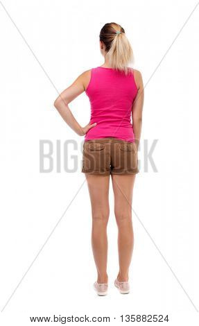 back view of standing young beautiful  woman.  girl  watching. Rear view people collection.  Isolated over white background. Blonde in brown shorts held up his right hand on his waist.
