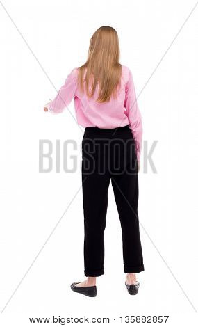 back view of young woman presses down on something. Isolated over white background. Rear view people collection. The girl office worker in black trousers presses his finger on the button.