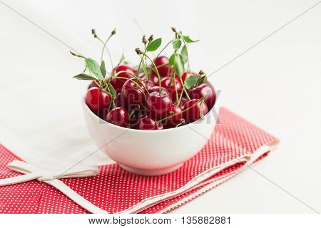 Freshly Picked Cherries With Stem And Leaves In A White Bowl