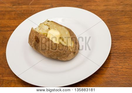 Hot baked potato on white plate with butter