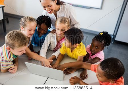 Happy teacher and pupils using laptop in classroom