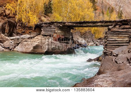 mountain river with the wooden bridge in autumn