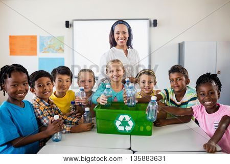 Portrait of pupils and teacher recycling in classroom