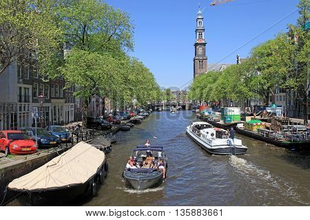AMSTERDAM, NETHERLANDS - MAY 8, 2016: People enjoy a boat ride in the canals of Amsterdam in sunny day. Amsterdam is the capital and most populous city of the Netherlands.