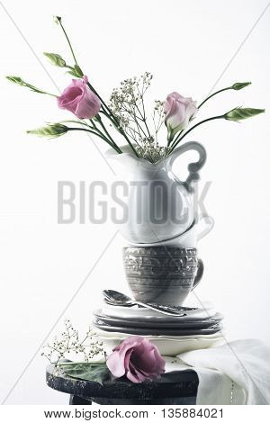Tableware with flowers. Plates, coffee cups, a pitcher of pink flowers on an old black stool. Consept with copy space for text.