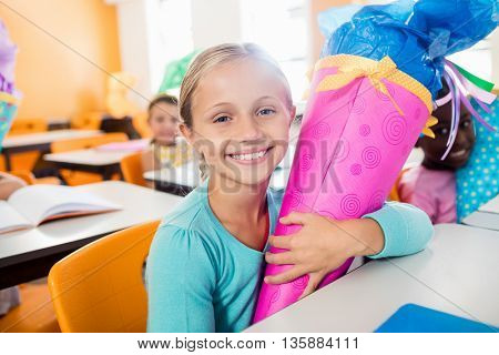 Portrait of a smiling pupil receiving a gift box in classroom