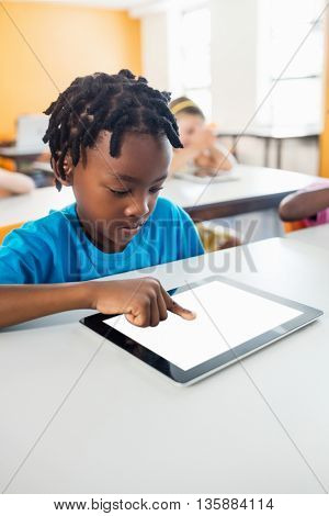 Little boy studying with tablet in classroom at elementary school