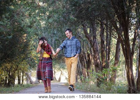 Loving couple in bright clothes walking along park alley holding hands and looking at each other