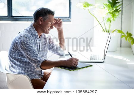 Serious man working at desk with laptop in modern office