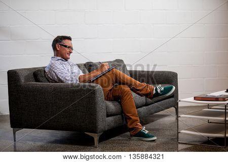 A businessman writing in a notebook in sofa