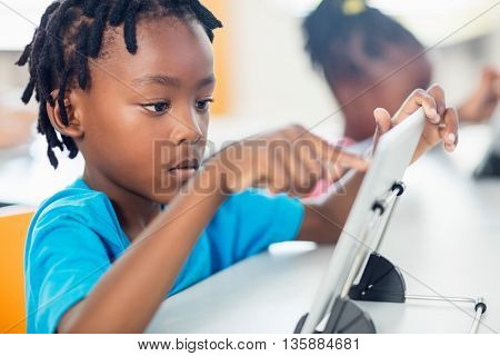 Close up view of pupil using tablet pc at desk in classroom