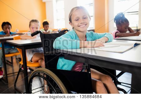 smiling pupil in wheel chair posing for camera at desk in classroom