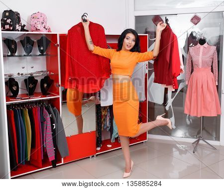 Young woman shopping in a clothing store. Woman shopping for dress in clothing retail store. Caucasian shopper girl choosing red dress in shop during sale. Woman shopping for dress. Fashion shopping