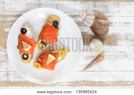 Tasty various italian sandwiches with seafood against rustic wooden background. Crostini with cheese red fish fillet lemon and sliced olives horizontal top view