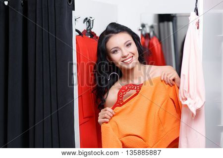 Can you bring me on more dress please. Fashionable young woman shopping in a clothing store. Woman shopper in a fitting room. Woman shopping for dress. Woman shopaholic. Fashion shopping