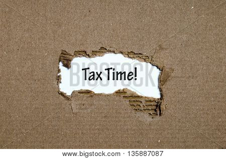 The word tax time appearing behind torn paper