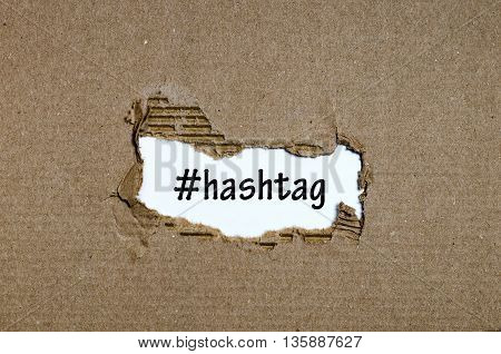 The word hashtag appearing behind torn paper