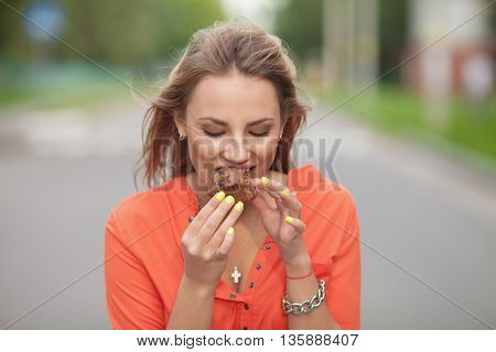 Cupcakes - woman eating cupcake in, Central Park. Business woman eating unhealthy food snack in lunch break smiling happy. Beautiful casual businesswoman.
