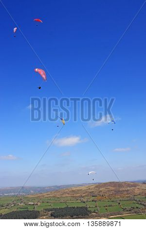 Paragliders flying their wings above Dartmoor, Devon