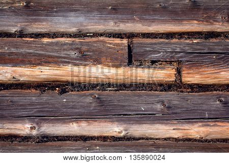 The wall made of wooden logs. The joint between the logs. Background