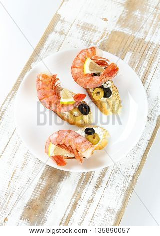 Tasty various Italian sandwiches with seafood against rustic wooden background. Crostini with cheese king shrimps lemon sliced olives on white plate top view