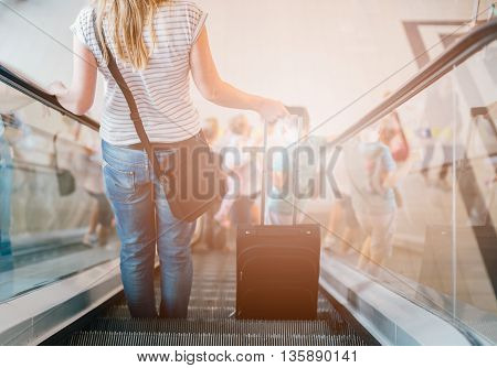 Woman With Her Suitcase On Escalator