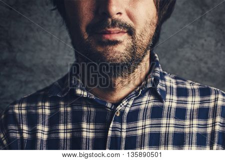Casual man in plaid shirt smiling thinking and contemplating low key selective focus portrait