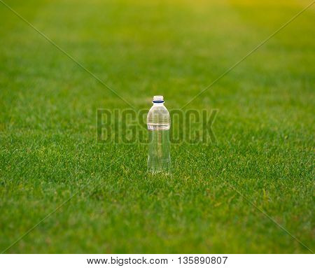 water bottle for fitnes on the green field