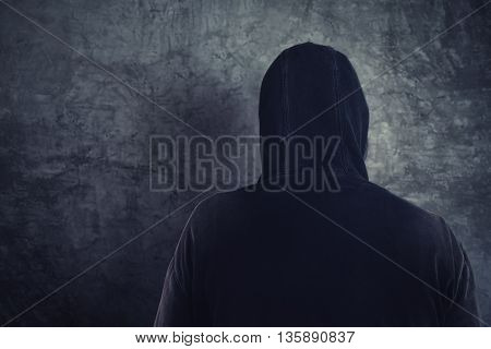 Unrecognizable hooded soccer hooligan from behind spooky criminal person in jacket with hood