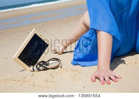 Woman's Hands And Leg With Chalkboard And Summer Time On It Against The Sea